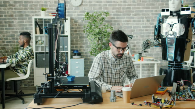 Young developer using laptop typing in office, 3d printer and robot are visible