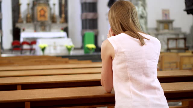 Young devoted religious woman praying in catholic church. Faithful catholic at european cathedral video