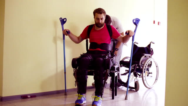 Young disable man in the robotic exoskeleton Young disable man in the robotic exoskeleton getting up from wheelchair in the rehabilitation clinic. Doctor helping him prosthetic equipment stock videos & royalty-free footage