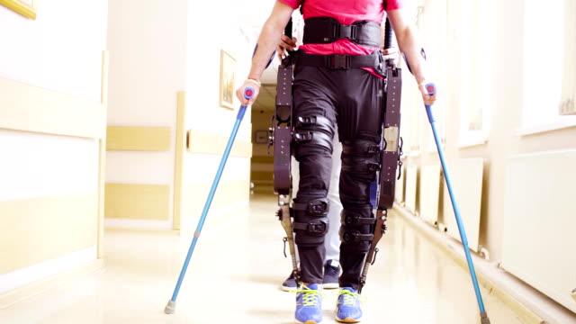 vídeos de stock e filmes b-roll de young disable man walking in the robotic exoskeleton - membro