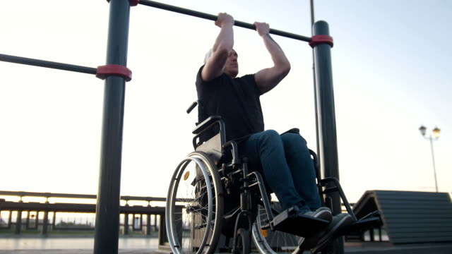 Young disabled man in wheelchair engaged on the crossbar outdoors video