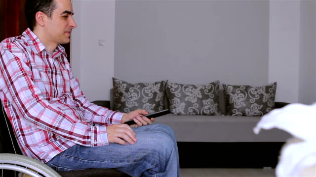 Young disabled man watching tv video