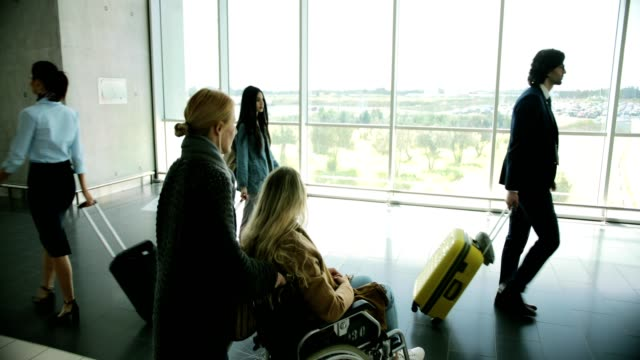 Young disabled woman on wheelchair looking out airport window