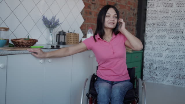vídeos de stock e filmes b-roll de young disabled woman talking phone and drinking coffee at table in home kitchen - pessoas com deficiência