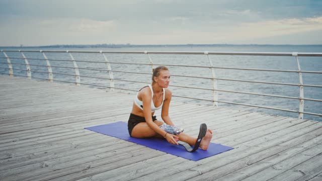 Young disabled woman training alone on pier near sea Young disabled woman training alone on pier near sea, sitting on fitness mat amputee stock videos & royalty-free footage