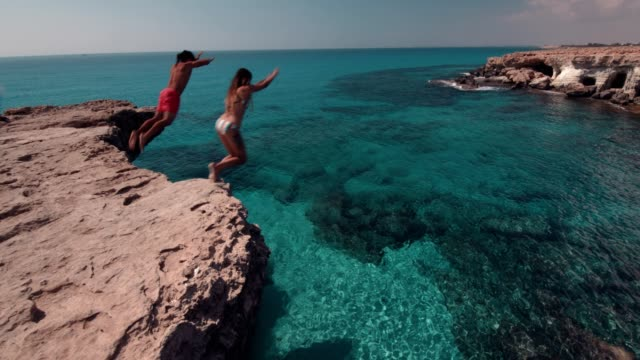 young divers couple jumping off cliff into the ocean - cliffs stock videos & royalty-free footage