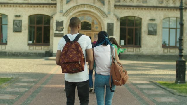 young diverse college students going to study - uniwersytet filmów i materiałów b-roll