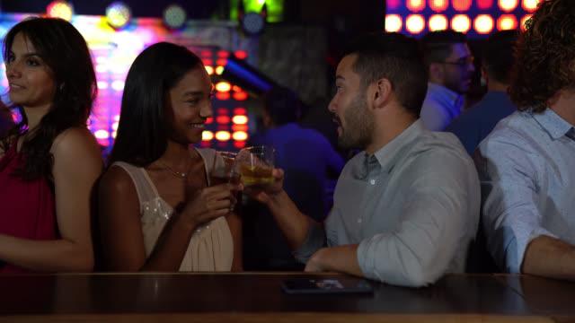 bir barda konuşurken ve gülümserken viskinin tadını çıkaran genç çift - flört etmek stok videoları ve detay görüntü çekimi
