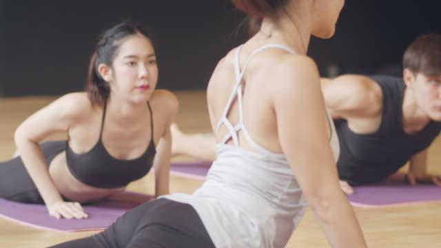 若い多様性のスポーツの人々は、インストラクターとヨガのレッスンを練習しています。フィットネススタジオで健康的なライフスタイルを行使する女性と男性の多民族グループ。スポーツ� - ヨガ点の映像素材/bロール
