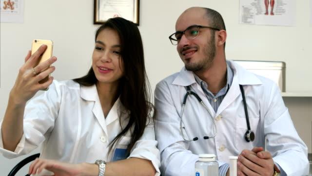 unga läkare och vacker sjuksköterska tar selfies på telefonen på deras skrivbord - hospital studio bildbanksvideor och videomaterial från bakom kulisserna
