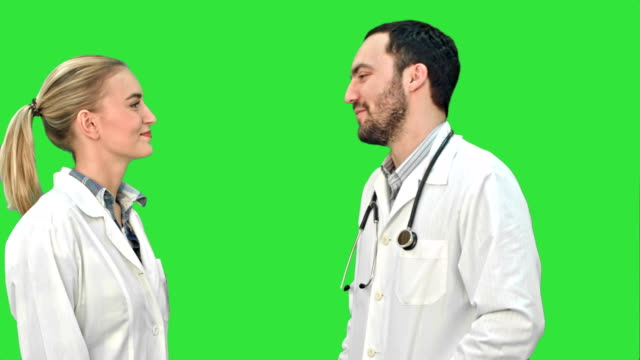 Young doctor joking on his collegue not give five on a Green Screen, Chroma Key video
