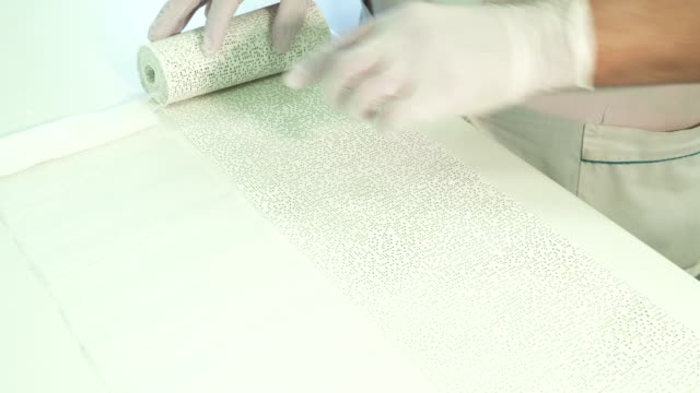 Young doctor unwinds roll with polyurethane tape on table indoors video