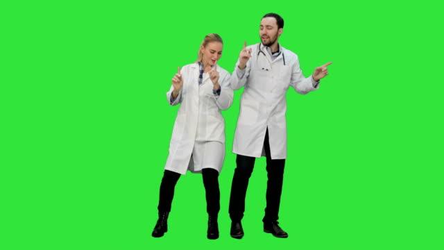 Jonge artsen in een goed humeur dansen en zingen liedjes op een groen scherm, Chromakey video