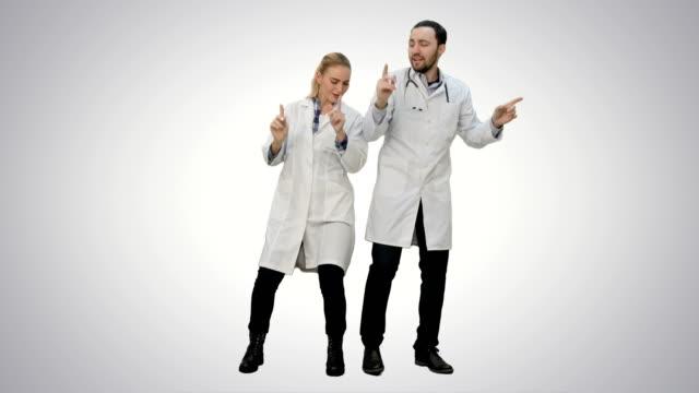 Jonge artsen in een goed humeur dansen en zingen liedjes op witte achtergrond video