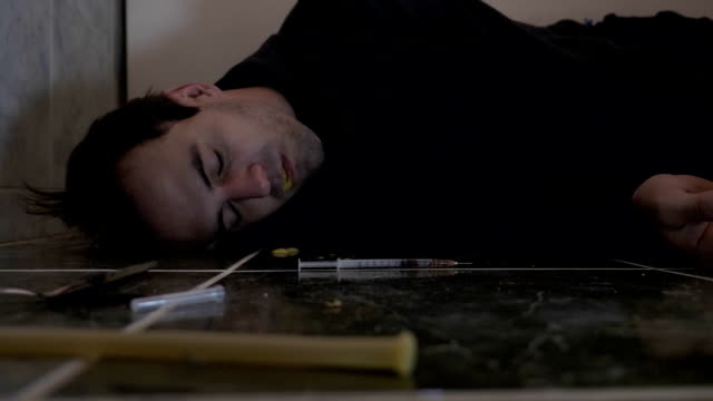Young drug addicted man shooting overdose of heroin in bathroom vomiting and falling unconsciously on the floor having spasms in slow motion video