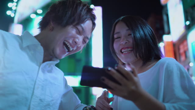 young east asian boy and girl couple talking, laughing, using mobile phone and sharing screen. in the background blurred advertising billboards and city lights at night. - свидание стоковые видео и кадры b-roll