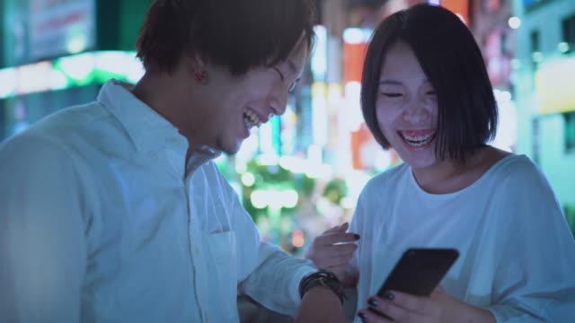 vidéos et rushes de est jeune garçon japonais et couple fille parler, rire, à l'aide de téléphone portable et partage d'écran. à l'arrière-plan flou panneaux publicitaires et les lumières de la ville pendant la nuit. - culture japonaise