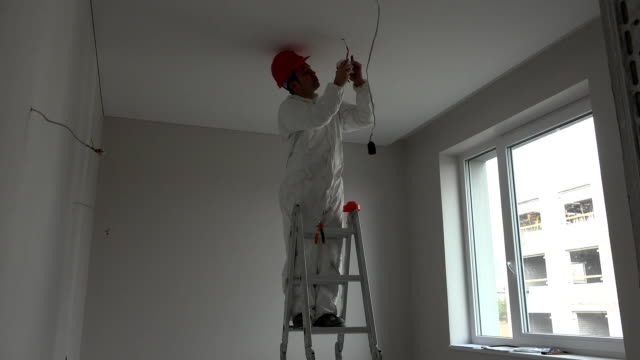 Young electrician installing smoke detector fire alarm on ceiling video