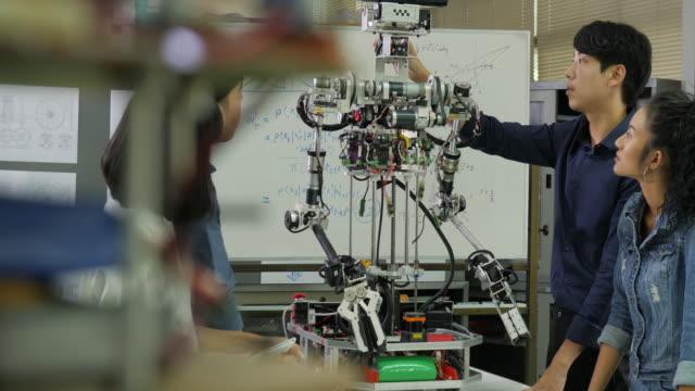 若いエレクトロニクス エンジニアのチームは、ワーク ショップでロボットの建設に協力します。チーム エンジニアは一緒にロボット プロジェクトを起動します。技術または技術革新の概念 - 機械部品点の映像素材/bロール