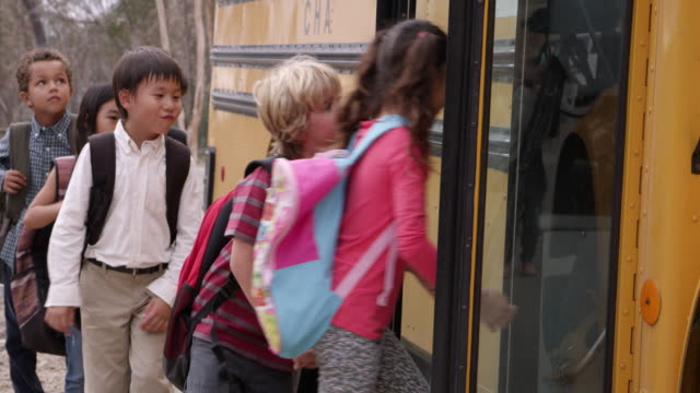 young elementary school kids boarding a school bus - school buses stock videos and b-roll footage