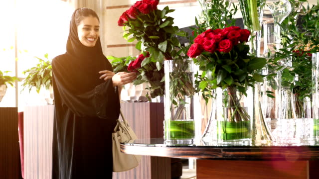 young emirati woman by the red roses - emirati woman 個影片檔及 b 捲影像