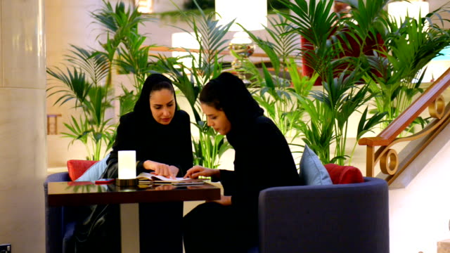 young emirati woman in a luxury cafe - emirati woman 個影片檔及 b 捲影像