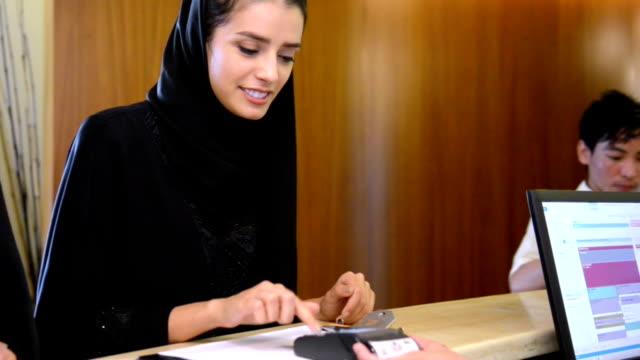 Young Emirati woman paying via credit card video