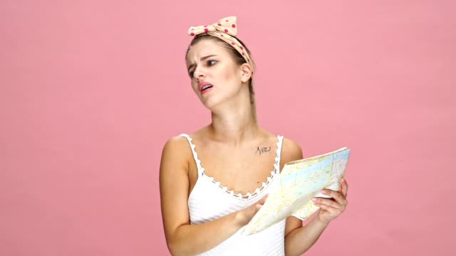 Young emotional caucasian woman holding map and mobile phone in hands over pink background. video