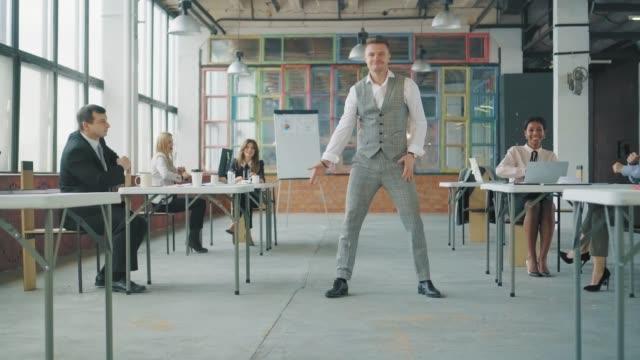 若い社員がオフィスで踊るのは楽しい。同僚はテーブルに座り、座って踊ります。ロフトスタイルのクリエイティブなオフィススペース。オフィスライフ。労働者は祝う。コワーキング ビデオ