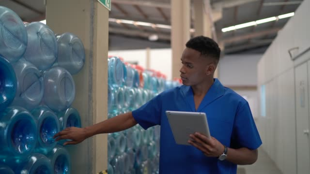vídeos de stock e filmes b-roll de young employee walking and using digital tablet in industry - caneca