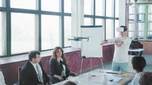 若いエンジニアが手のジェスチャーと仮想メガネを使用してドローンを制御します。成功。従業員は手をたたいてお互いを祝福します。コワーキングスタートアップチーム。オフィスワーカ� ビデオ