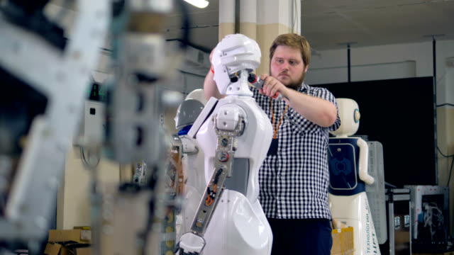 A young engineer disassembles a robots head. A technician works on removing parts on a robots head. robot stock videos & royalty-free footage