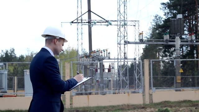 vidéos et rushes de un jeune ingénieur à l'arrière-plan d'une centrale électrique écrit des données à une tablette - inspecteur