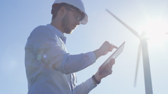 young engineer using tablet computer outdoors. wind turbines on background. - turbina a vento video stock e b–roll