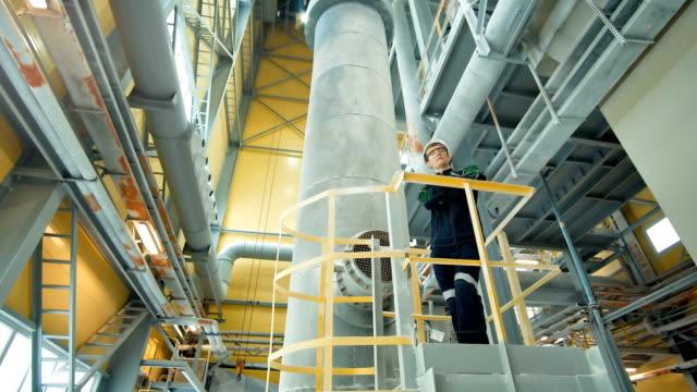 stockvideo's en b-roll-footage met jonge ingenieur dragen beschermende helm poseren in moderne fabriek - raffinaderij