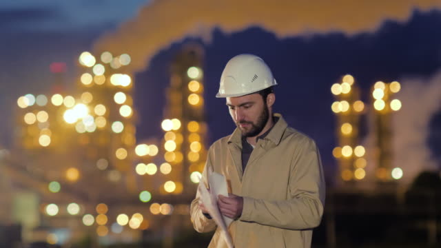 Young engineer with blue print on the background of oil factory at night