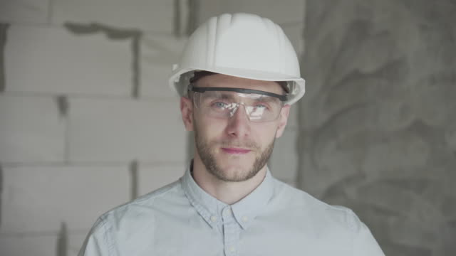 Young engineer-architect in a bright room with glasses and a construction helmet looks at the camera and shows like