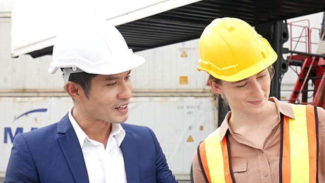 Young Engineers standing in the shipping yard tracking the cargo inventory and checking container box for safety. Young Engineers standing in the shipping yard tracking the cargo inventory and checking container box for safety. occupational safety and health stock videos & royalty-free footage