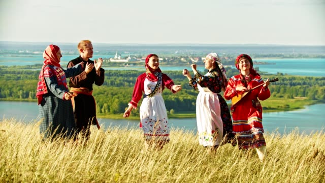 young ensemble in traditional russian clothes dancing on the field by the music - славянская культура стоковые видео и кадры b-roll