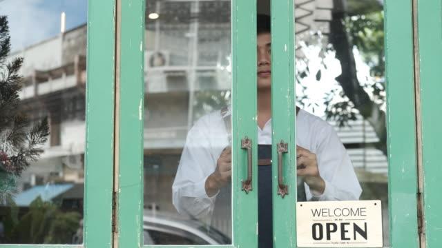 il giovane imprenditore apre la porta al mattino nella sua caffetteria. - aperto video stock e b–roll