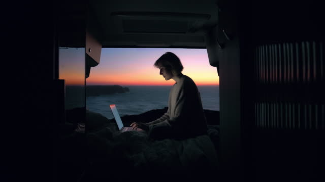 a young entrepreneur woman is working on her computer in a camper van. - car chill video stock e b–roll