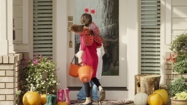 Young ethnic children running between houses trick or treating gleefully video