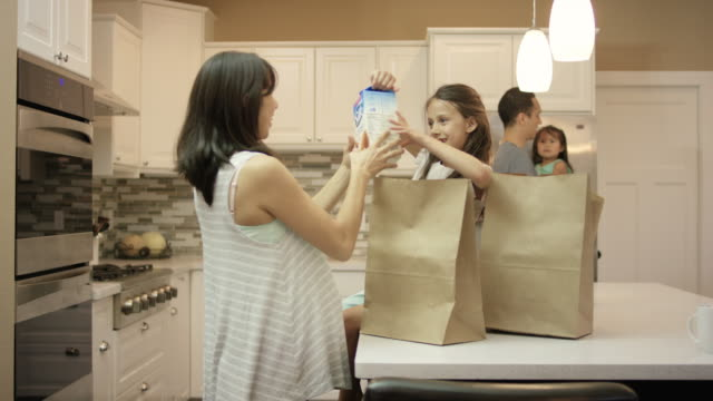 young ethnic daughter helping her pregnant mother put groceries away - grocery home video stock e b–roll