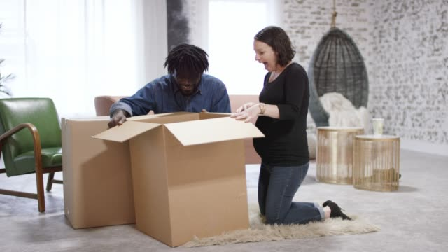 Young Ethnic Family Unpacking With Their Toddler Son