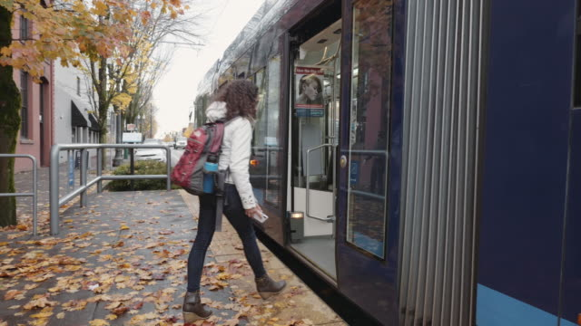 Young Ethnic Female Adult Boarding a Streetcar A young ethnic woman wearing a backpack boards a streetcar on a fall afternoon bus stop stock videos & royalty-free footage