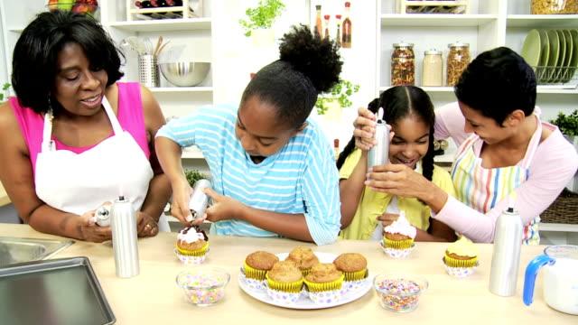 giovane ragazza etnica madre nonna torte dolci di cucina - cupcake video stock e b–roll