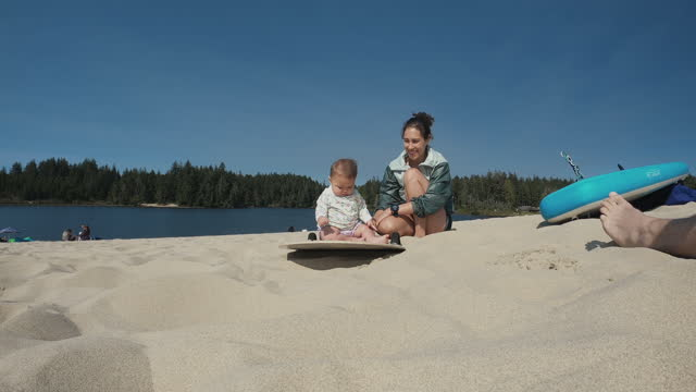 Young ethnic mother playing in the sand with her baby daughter on vacation