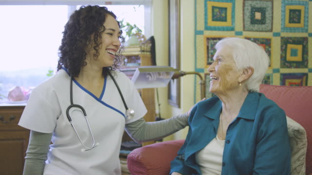 young ethnic nurse talking with elderly woman in facility - età miste video stock e b–roll