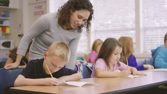 Young ethnic teacher works with her elementary school students in class video