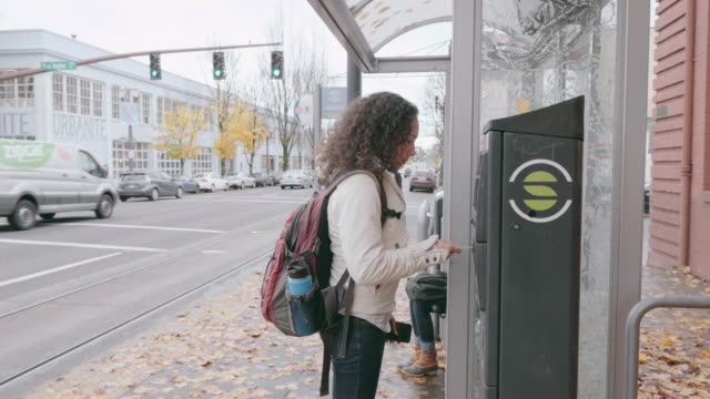 giovane donna etnica che paga il biglietto del tram - fare video stock e b–roll